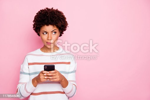 Photo of pretty dark skin lady holding telephone doubtful about new instagram, post wear white striped pullover isolated pastel pink color background