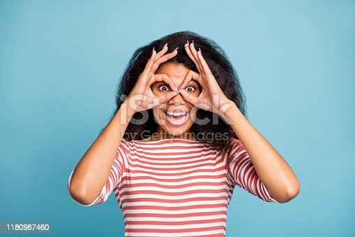 Photo of pretty dark skin lady looking through hands specs watching, far away wear casual white red striped sweater isolated pastel blue color background