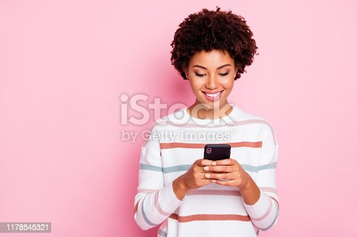 istock Photo of pretty dark skin wavy lady holding telephone addicted to internet reposts and comments wear white striped pullover isolated pastel pink color background 1178545321