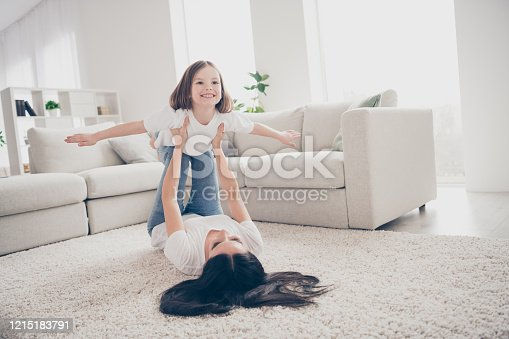 Photo of pretty funny little girl young mommy holding daughter, hands above floor having fun pretending airplane flight lying carpet spend time weekend together home indoors