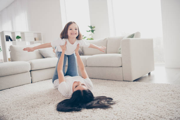 Photo of pretty funny little girl young mommy holding daughter hands above floor having fun pretending airplane flight lying carpet spend time weekend together home indoors stock photo