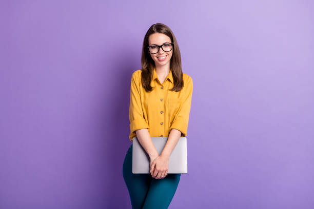 Photo of pretty girl hold laptop look camera wear glasses yellow shirt blue trousers isolated purple color background stock photo