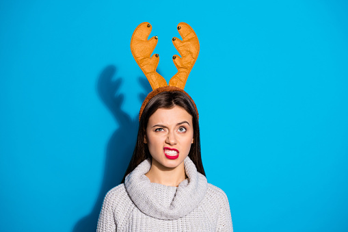 Photo of pretty lady dislike wearing toy horns knitted pullover isolated blue background