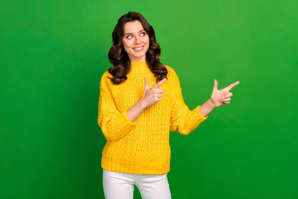 Photo of pretty lady hold hands directing fingers look empty space advising offer novelty wear knitted yellow pullover white trousers isolated bright green color background stock photo
