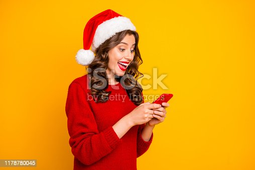 istock Photo of pretty lady holding telephone in hands wear knitted pullover and santa hat isolated yellow background 1178780045
