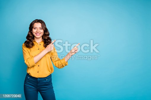 Photo of pretty sale manager lady indicating finger empty space, advising new product low discount price wear yellow shirt trousers isolated blue color background
