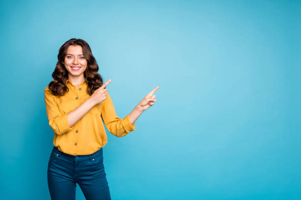 Photo of pretty sale manager lady indicating finger empty space advising new product low discount price wear yellow shirt trousers isolated blue color background stock photo