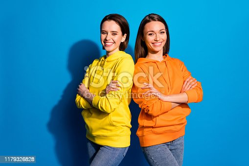istock Photo of pretty two girlfriends lady standing back-to-back in good mood crossing arms wear casual bright hoodies and jeans isolated blue color background 1179326828