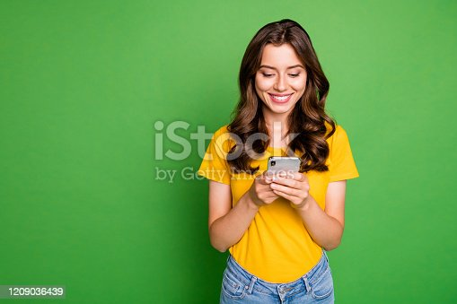 Photo of pretty wavy lady holding telephone hands reading website, blog new interesting post wear casual yellow t-shirt jeans isolated bright green color background