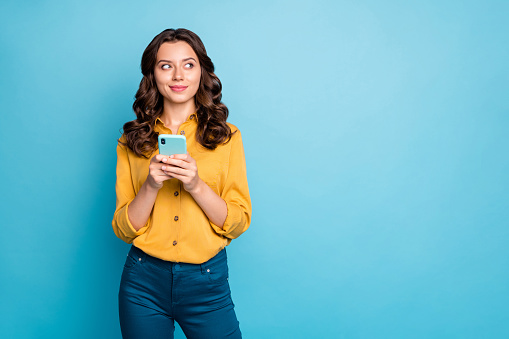 Photo of pretty wavy lady holding telephone hands thinking over creative post text idea looking side empty space wear yellow shirt trousers isolated blue color background