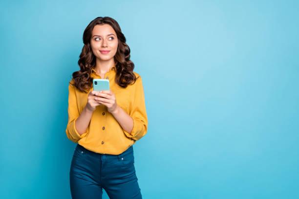 照片漂亮的波浪夫人拿著電話手思考創意後文本想法看側空空間穿黃襯衫褲子孤立的藍色背景 - 僅一名女人 個照片及圖片檔