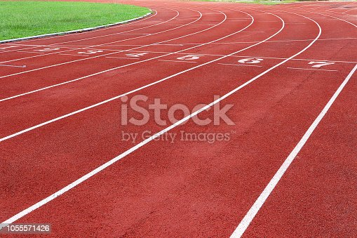 Photo of red running track for competition or exercise, as background. Sports concept. Colorful tone.