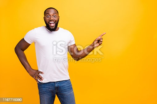 istock Photo of rejoicing overjoyed excited encouraged casual ecstatic man holding his hand on waist pointing at emptiness while isolated with vivid background 1167715390