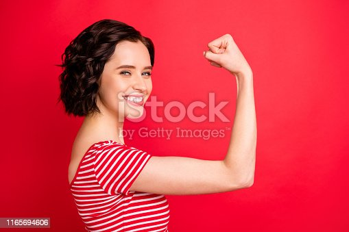 istock Photo of rejoicing wavy curly woman after having done two pushups while isolated with red background 1165694606