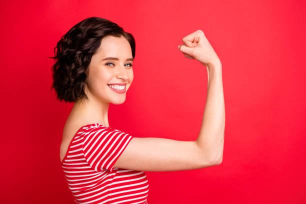 在用紅色背景隔離時做了兩次俯臥撐後,歡欣鼓舞的波浪捲曲婦女的照片 - 肌肉發達 個照片及圖片檔