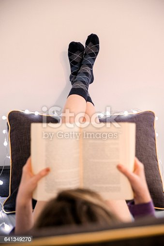 501914364istockphoto Photo of Relaxed woman lying in bed reading a book 641349270