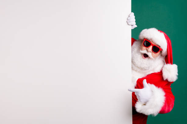 Photo of retired stylish grandfather grey hair beard direct finger white empty board offer best option wear red santa x-mas costume coat gloves sunglass cap isolated green color background stock photo