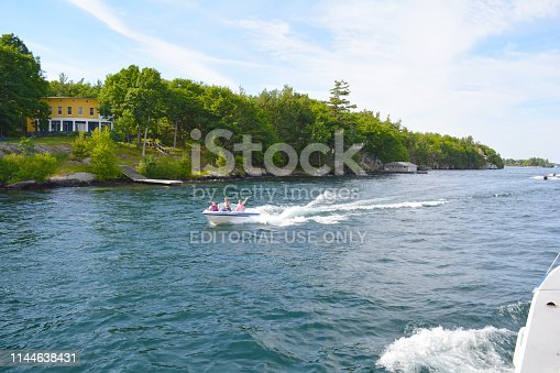 St Lawrence River's Thousand Islands, Ontario Canada- June 19, 2016: Photo of river with boat on the St. Lawrence River. Kingston in Ontario, Canada - USA border. Unfiltered, natural lighting. Tourist routes.