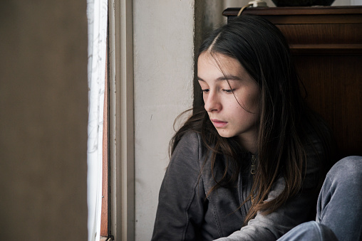 istock Photo of Sad girl looking out of window 638915404