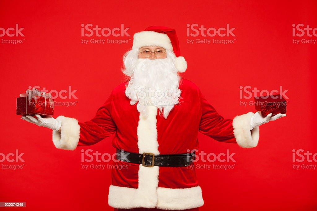 Photo of Santa Claus gloved hands holding red giftbox zbiór zdjęć royalty-free