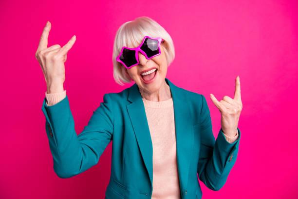 foto av skrikande vit haired skrika gungande mogen kvinna bär beige tröja grön jacka star formade rosa glasögon isolerade över rödbrunt levande färg bakgrund - celebrities of age bildbanksfoton och bilder