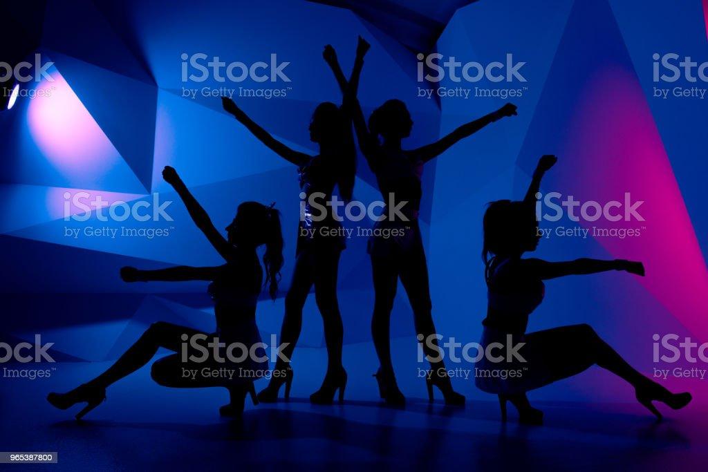 Photo of silhouettes of four sexy posturing girls in dark zbiór zdjęć royalty-free