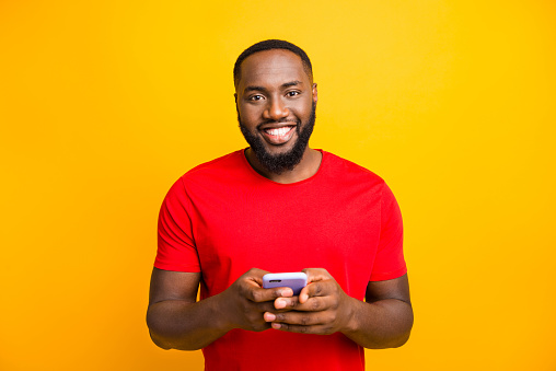 istock Photo of simple good cute handsome black man holding his phone with both hands smiling at camera while isolated with yellow background 1169766738