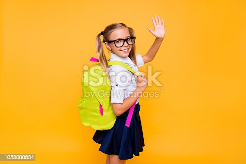 istock Photo of small girl turned around half a turn and waving hand look at camera isolated on bright yellow background with copy space for text 1058000834