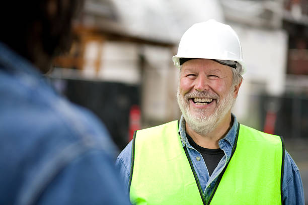 Photo of smiling bearded construction worker in green vest stock photo
