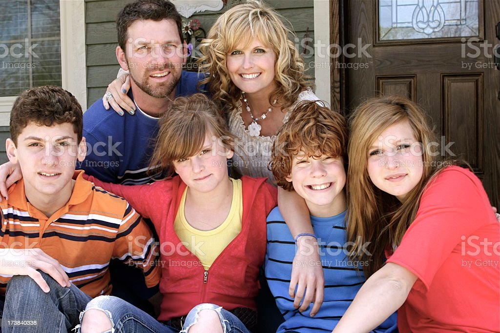 A photo of smiling family members seated on a front porch stock photo