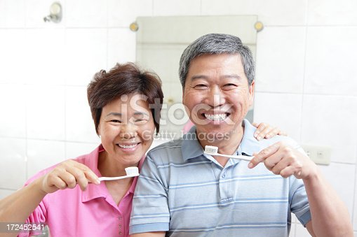 istock Photo of smiling senior couple holding toothbrushes 172452541