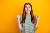 istock Photo of smiling shouting cheerful positive girlfriend having found dress she has wanted to obtain got cheaper by half while isolated with yellow background 1166389484