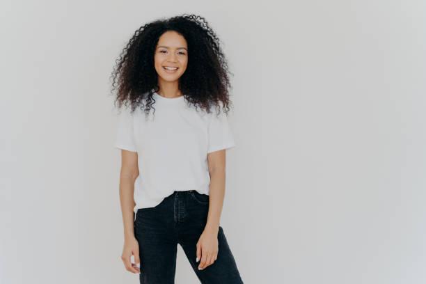 foto van lachende vrouw met krullend donker haar, heeft slanke figuur, draagt wit t-shirt en zwarte jeans, heeft blijde gezichtsuitdrukking, modellen tegen witte achtergrond, kopieer ruimte voor uw advertentie-inhoud - zwarte spijkerbroek stockfoto's en -beelden