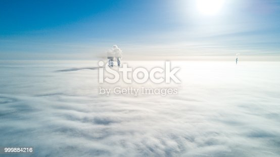 Photo of smoking pipes from a drone flying through the clouds, over the fog