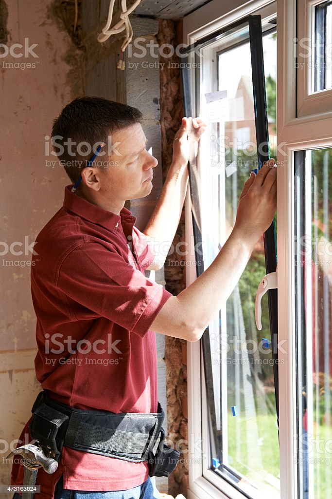 A photo of someone installing a window on an exterior wall stock photo