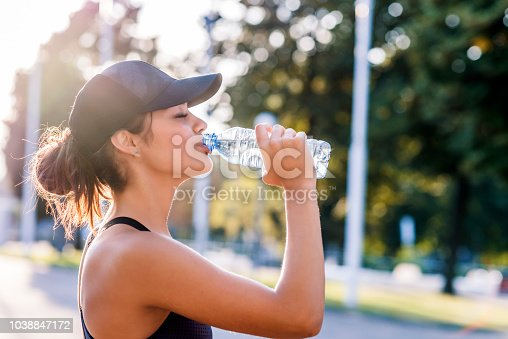 Photo of young Woman drinking water from bottle. Caucasian female drinking water after exercises or sport. Beautiful fitness athlete woman wearing hat drinking water after work out exercising on sunset evening summer,outdoor portrait.