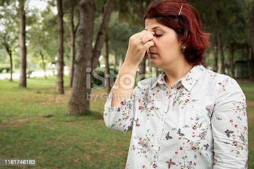 Stock Photo of Woman With Pole Allergies, Alone in the woods.  Woman scratching her eyes.