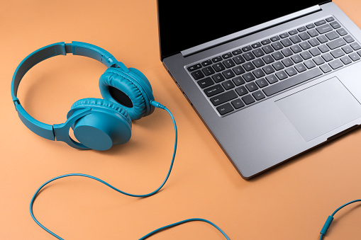 Photo of stylish modern computer or notebook and blue cyan headphones over beige background