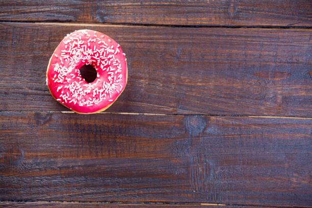 photo of tasty glazed donut on the wonderful brown wooden background - rosa tarnfarbe stock-fotos und bilder