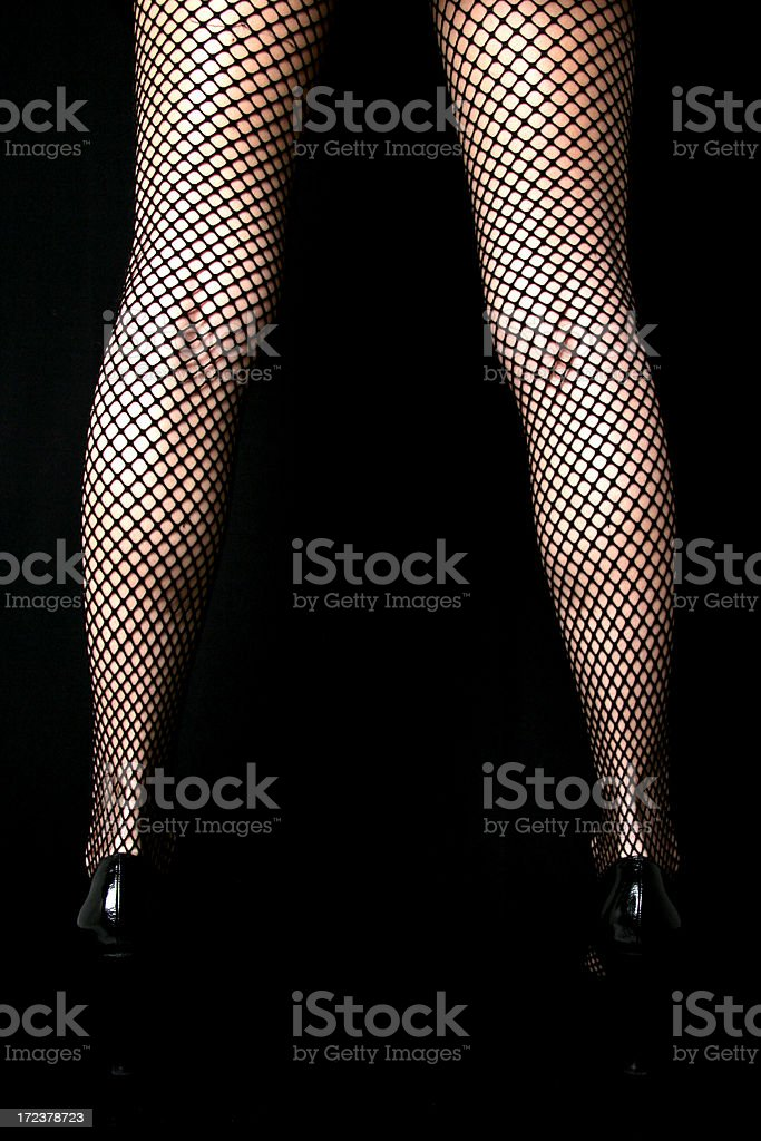 Photo of the back of woman's legs clad in fishnet stockings stock photo