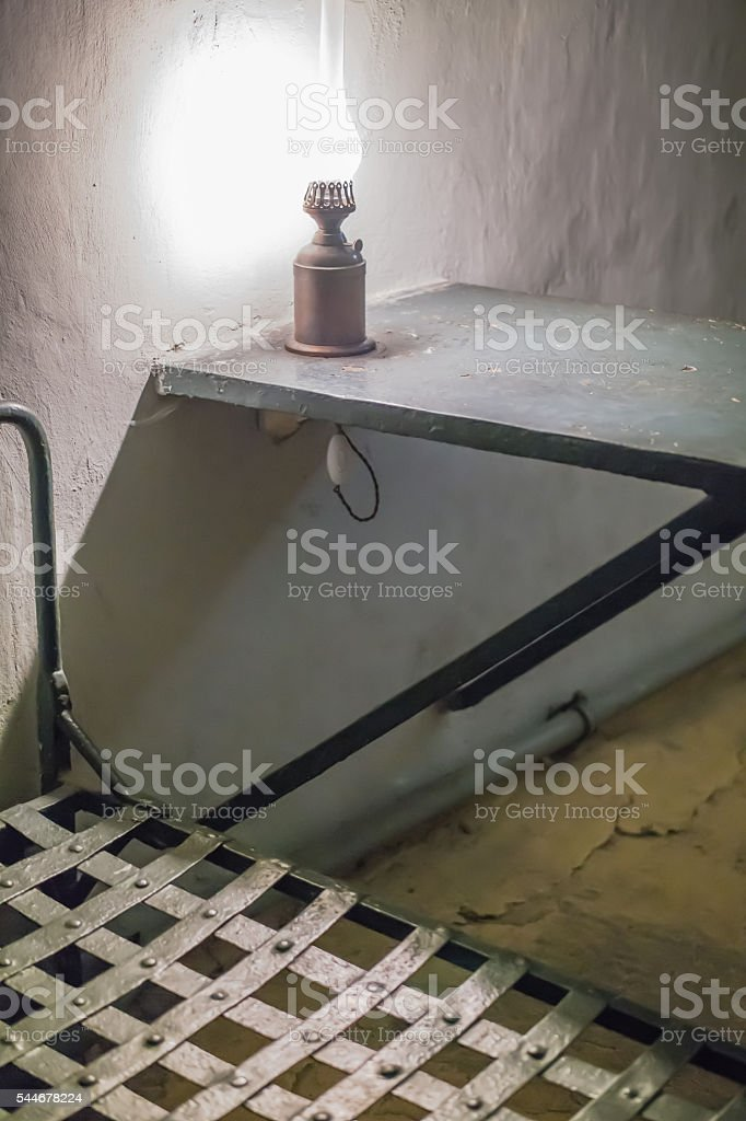 Photo of the interior  the prison. bed and desk with stock photo