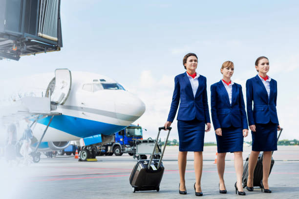 Photo of three confident flight attendants walking against airplane in airport stock photo
