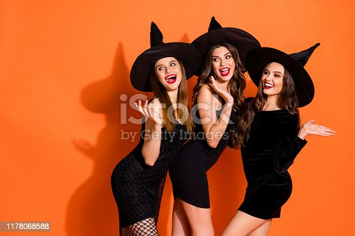 Photo of three cruel witch ladies calling handsome guys using magic powers wear short black dresses and wizard hats isolated orange color background