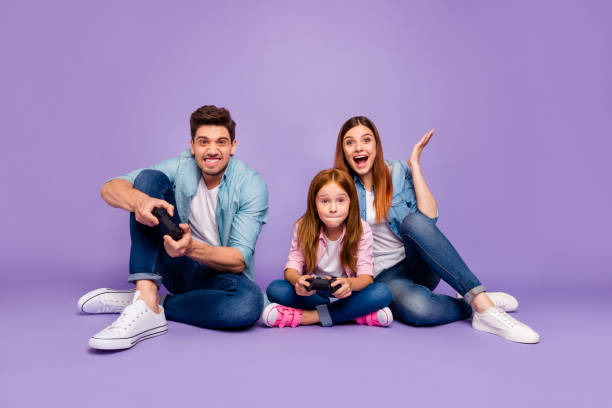 photo of three family members sitting floor trying hard to win team game wear casual clothes isolated purple background - man joystick imagens e fotografias de stock