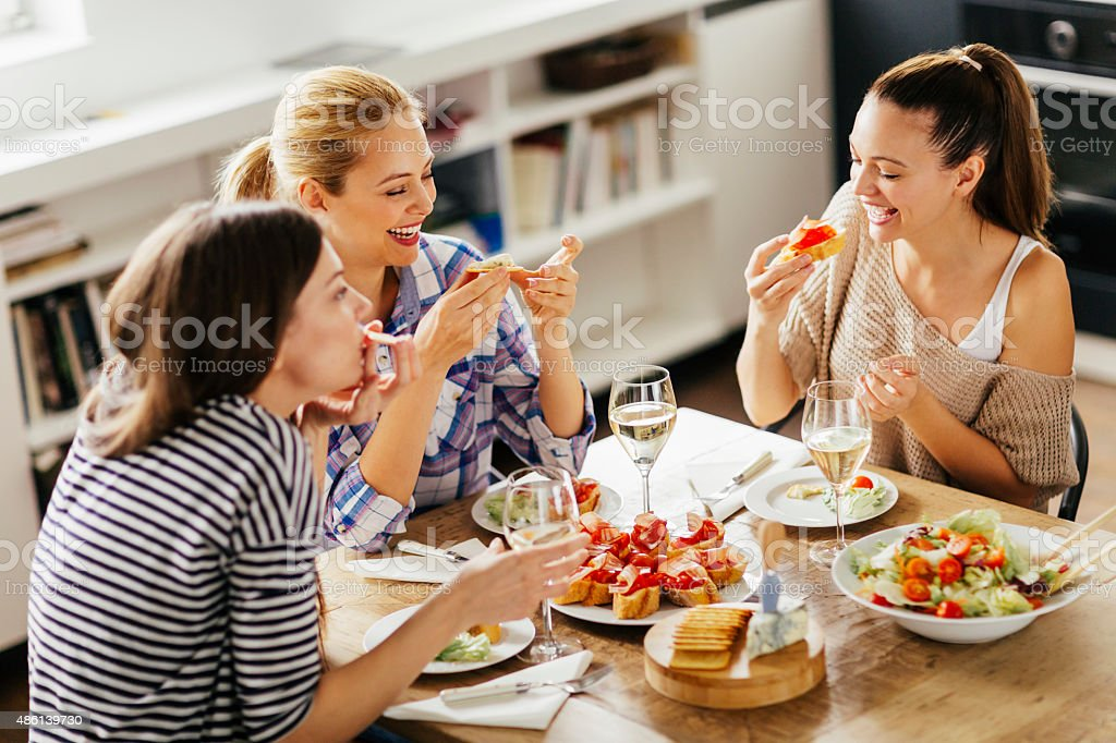 Photo of three women enyoing appetizers and wine at home stock photo