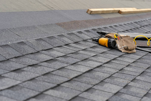 photo of toolbelt with instrument and nail gun lying on asphalt or bitumen shingle on top of the new roof under construction residential house or building - {{asset.href}} imagens e fotografias de stock