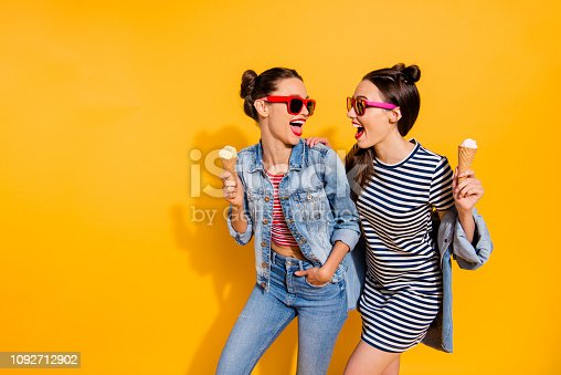 1092709104 istock photo Photo of two brunette hair lady in glasses spectacles isolated on yellow background hold sugar tasty yummy delicious sweet appetiser snack in hands look each other make beaming hollywood toothy smile 1092712902