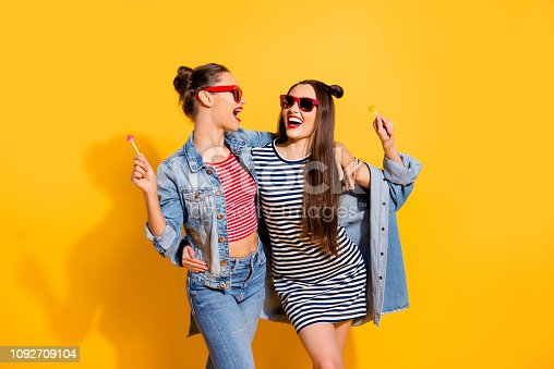 istock Photo of two brunette hair lady look each other stand isolated on yellow wall in glasses spectacles hold sugar sweet yummy calories caramel confectionery dessert in hands 1092709104