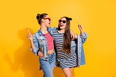 Photo of two brunette hair lady look each other stand isolated on yellow wall in glasses spectacles hold sugar sweet yummy calories caramel confectionery dessert in hands