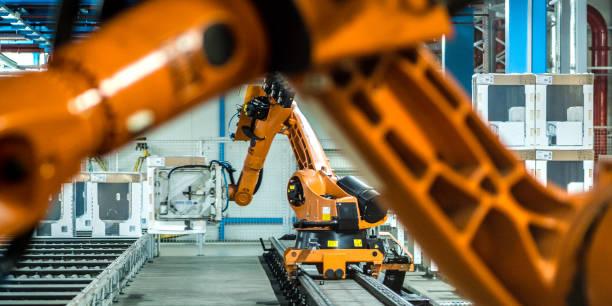 Foto von zwei Roboterarmen, die in einer Fabrik arbeiten – Foto